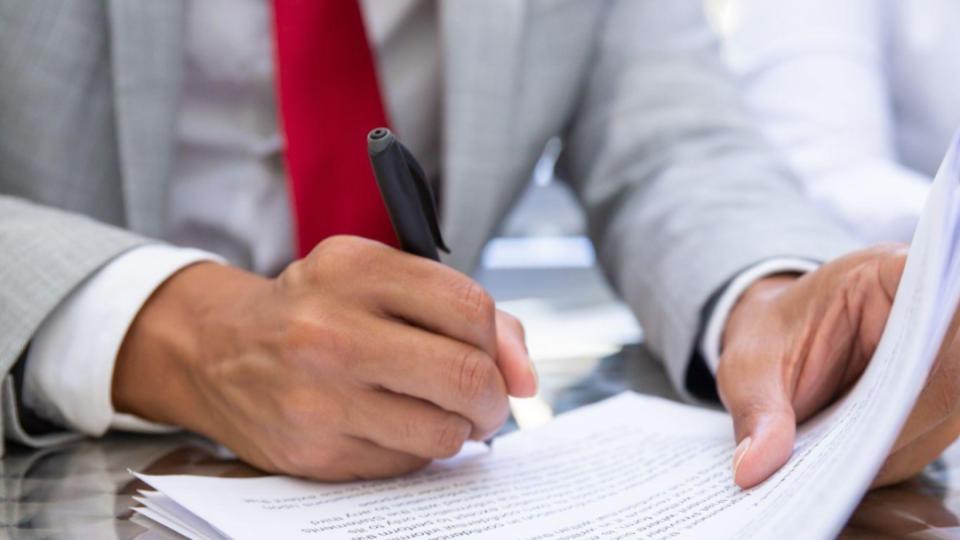 homem formal assina documento
